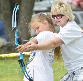 Bonnie Webster of Mt. Roberts Baptist Church helps Megan Settles of Greensburg learn to shoot a bow and arrow.