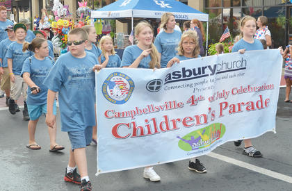 Asbury Church members, who sponsored the event, hold a banner at the beginning of the annual children's parade.