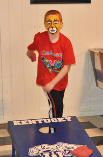 Bryten Close tosses bean bags on a cornhole board at the Kid SpOt Center's Autism Awareness event on Saturday.