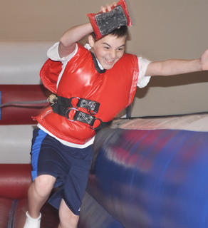 Drew Woodcox tests his endurance on one of the many inflatables available at the Kid SpOt Center's Autism Awareness event on Saturday.