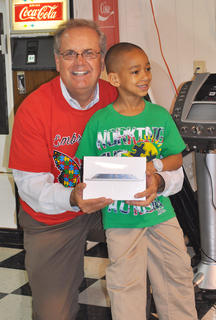Zakias Newby, shown with Campbellsville Mayor Tony Young, smiles after winning an iPad mini at the Kid SpOt Center's Autism Awareness event on Saturday.