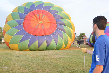 Bob Gaidzik of Lexington holds a hot air balloon in place as it is inflated.
