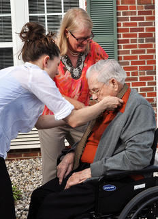 Rhodem Skaggs gets help with his tie from activities coordinator Brianne McKinney, left, and his daughter, Linda Collins, before the prom at Bluegrass Way Assisted Living on Saturday.
