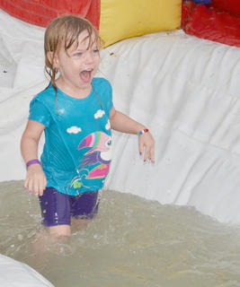 Brooklyn Williamson, 3, of Campbellsville, laughs as she splashes herself on a slide at the Family Fun Zone.