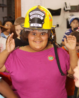 Tynisha Richerson, 8, a third grader at Campbellsville Elementary, tries on a firefighter's helmet during a visit to the Campbellsville Fire Department.
