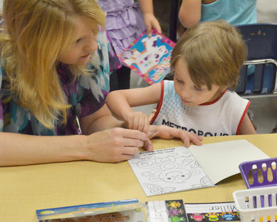 Campbellsville Elementary School teacher Chanci Patterson helps kindergartener Logan Miller color before the school day starts.