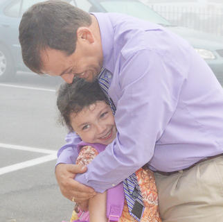 Campbellsville Elementary School second-grader Willow McDaniel gives her principal, Ricky Hunt, a hug as she walks into school.
