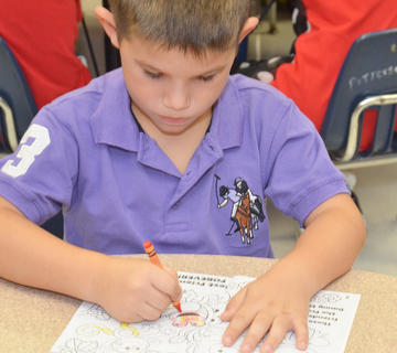 Campbellsville Elementary School kindergartener Kace Eastridge colors before class begins.