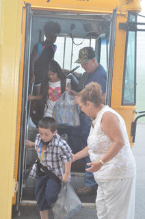 Lois Kemp, preschool assistant, helps Campbellsville Elementary School students Myles Wright, in front, and Leticia Escudero off the bus.