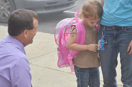 Campbellsville Elementary School kindergartener Ellie Wise isn't so sure about talking to her principal, Ricky Hunt, on the first day of school.