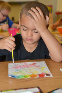 Jaden Barbee paints a picture in Chanci Patterson's CES kindergarten class during his first day of school.
