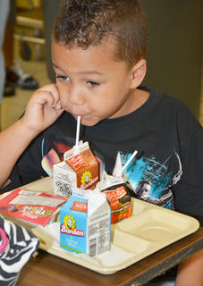 CES student Zarek Stone drinks milk during breakfast on the first day of school.