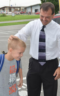 CES Principal Ricky Hunt gives student Konner Forbis a pat on the head to welcome him back to school.