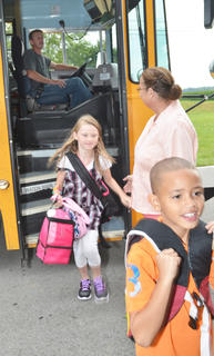 CES assistant Lois Kemp helps students get off the bus Tuesday morning.