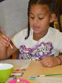 Kindergarten student Narissa Barnett paints a picture in Chanci Patterson's class at CES on her first day of school.