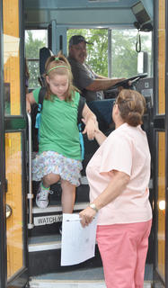 CES assistant Lois Kemp helps Aaliyah Nunez off the bus.