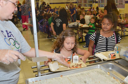 CES students Ivy Lawler, at left, and Alyssa Lofton walk through the breakfast line on Tuesday morning. All Campbellsville students will receive free breakfast and lunch again this year.