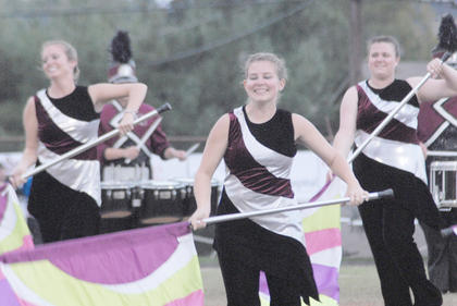 Thirteen area bands competed at the annual Taylor County Marching Invitational on Saturday at Taylor County High School. CU color guard members, from left, Kinly Bertram of Monticello, Andrea Bault of Campbellsville and Stacey Hurt of Cadiz perform on Saturday.