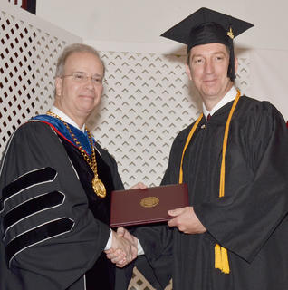 Kirk Anderson of Campbellsville poses for a photo with Dr. Michael Carter, CU's president, as he receives his Bachelor of Science degree in organizational management.