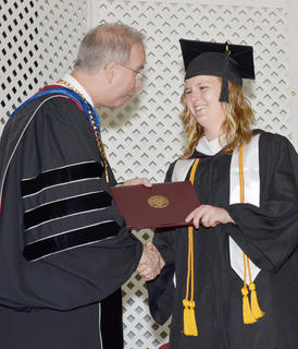 Rebekah Carl of Campbellsville smiles as Dr. Michael Carter, CU's president, gives her a Bachelor of Science degree in exercise science and sports medicine.