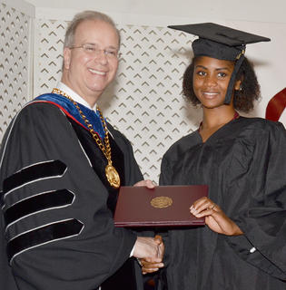 Starsha Fant of Campbellsville poses with Dr. Michael Carter, CU's president, after receiving her Bachelor of Science in Business Administration degree in marketing.
