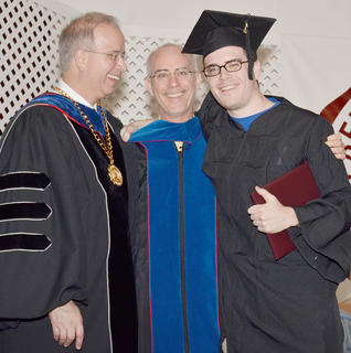 Peter Hurtgen, at right, hugs his father, Dr. John Hurtgen, dean of the School of Theology at CU, after his father presented him his Bachelor of Science Degree in Business Administration in accounting. At left is Dr. Michael Carter, CU's president.