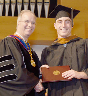 Spencer Adams of Campbellsville poses with Dr. Michael Carter, CU president, as he receives his master's degree in organizational leadership.