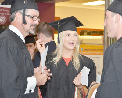 Crystal Lackey of Bloomington Springs, Tenn., talks with her fellow graduates before the start of the ceremony.