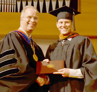 Alan Haven of Campbellsville poses with Dr. Michael Carter, CU president, as he receives his master's degree in organizational leadership.