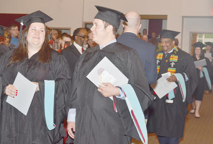 Charity Powell of Brandenburg and Christopher Price of Campbellsville share a laugh as their fellow graduates file into Ransdell Chapel. They received master's degrees in marriage and family counseling.
