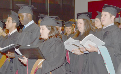 Graduates sing a hymn during Friday's ceremony.