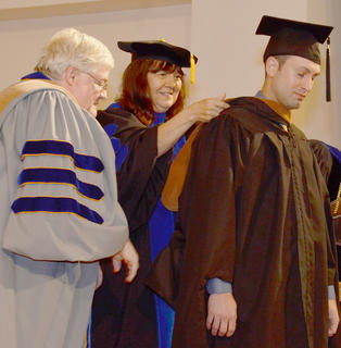 John Roution of Campbellsville is hooded as he receives his master's degree in business administration.