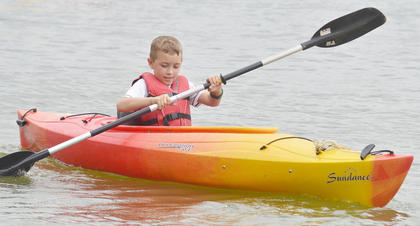 Kayden Long of Campbellsville rides a canoe at Camp Kentahten.