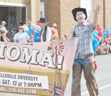 "Taylor County PVA Chad Shively, who was a part of the cast of ""Oklahoma,"" which was presented at Campbellsville University, waves to the crowd."