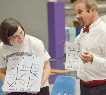 Grace Arnold smiles after she plays a game of tic-tac-toe with magician Mark Comley. Comley drew a picture of what their game would look like before Project Graduation on Saturday and, when comparing it to Arnold's board, it's the same.