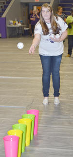 Breanna Underwood tosses a ball into metal containers.