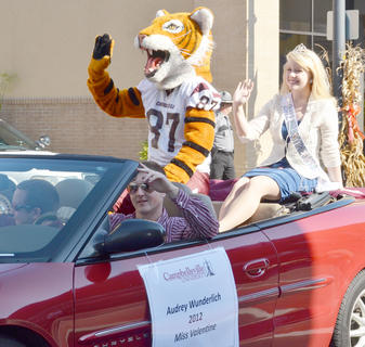 CU's mascot, Clawz, and Audrey Wunderlich, CU's 2010 Miss Valentine, wave to the crowd during the annual Homecoming parade.