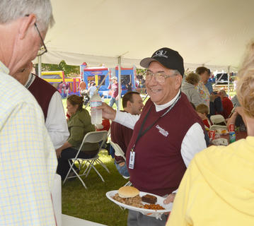 Al Hardy, the former dean of academic support at CU, gets a plate of food during the Homecoming festival on Saturday.