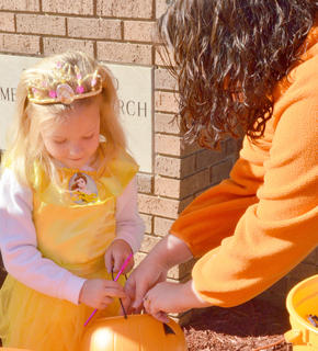 Michelle Stewart, 4, dressed as a princess, collects candy from Jacki Goodson, children&#039;s director at First United Methodist Church.