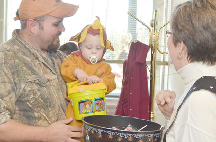 Jeremy Pyles holds his son, Brantley, 18 months, as he collects candy at Wise, Buckner, Sprowles & Associates from receptionist Kathy Bush.