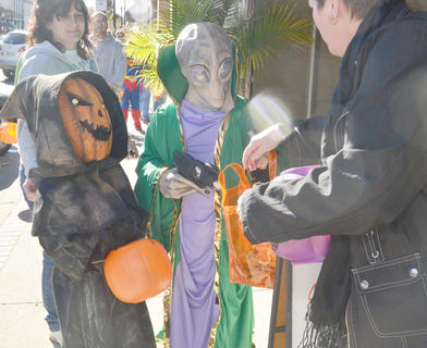 Ansley Bell, 6, and Wesley Bell, 11, dressed as a pumpkin head and alien, respectively, trick-or-treat at Mitchell&#039;s Men&#039;s Wear.