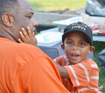 Marlon Hoskins of Campbellsville holds his son, Zaemar, 4, at the Durham reunion.