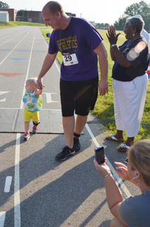 David Petett walks his daughter across the finish line at the 2k run/walk.
