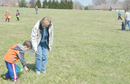 Children scramble to find as many Easter eggs as they can at Miller Parking Walking Track.