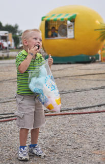 Layne Fischer enjoys some cotton candy in front of a lemonade booth.
