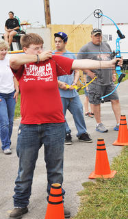 Amina Newcomb aims for the bullseye at the On Target for Christ Archery booth.