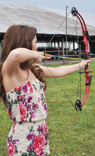 Taylor Dile tests her archery skills at the On Target for Christ Archery booth.