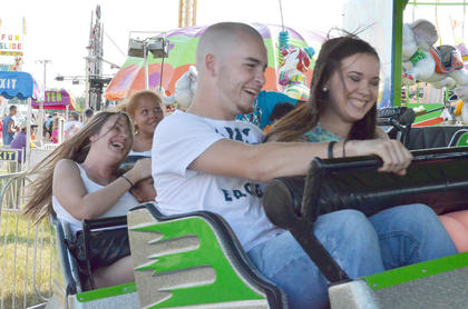 Fairgoers smile as their ride goes faster and faster.