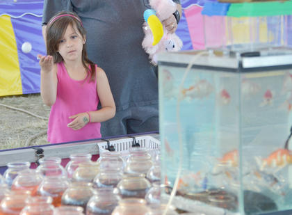 Izzy Rummage of Lebanon takes her best shot at winning a goldfish at the fair as her father, Tony, watches.