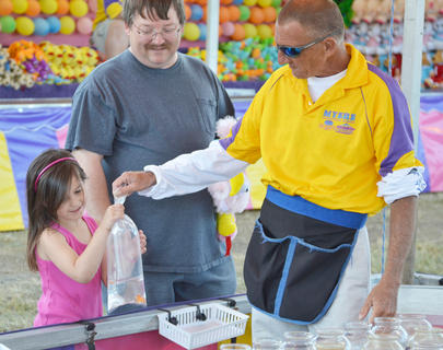 Izzy Rummage of Lebanon smiles as she wins a goldfish at the fair as her father, Tony, watches.